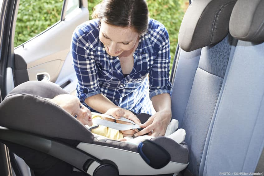 woman putting a baby into it's car seat facing the rear in a car
