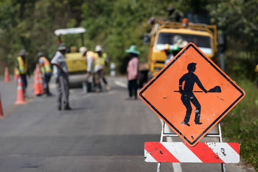under construction symbol on an orange sign with construction workers working on the road in the background