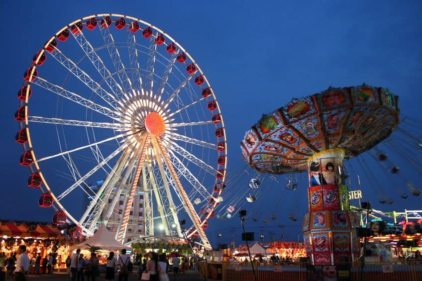 a carnival with a ferris wheel and swing ride lit up