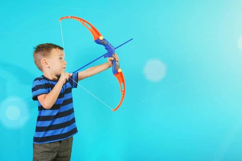 boy shooting a toy bow and arrow against a blue background