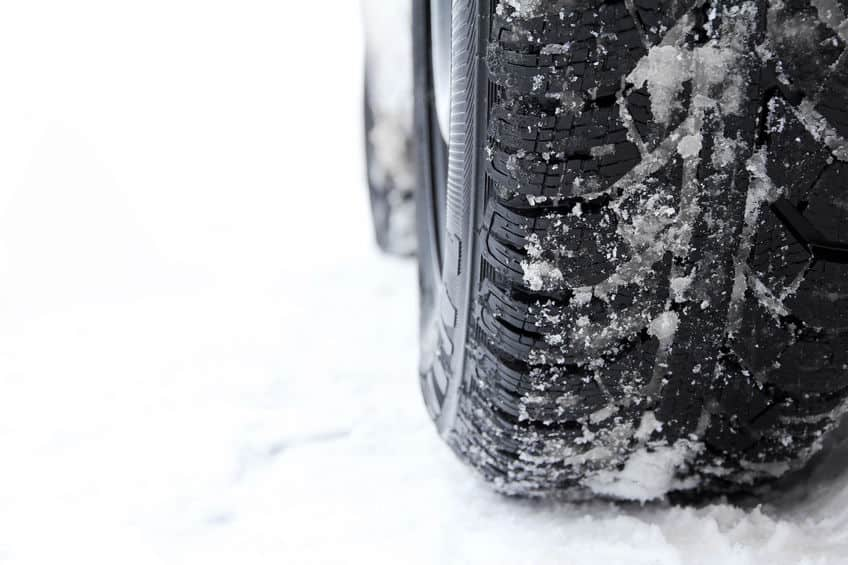 close up of snow tires against a snow covered ground
