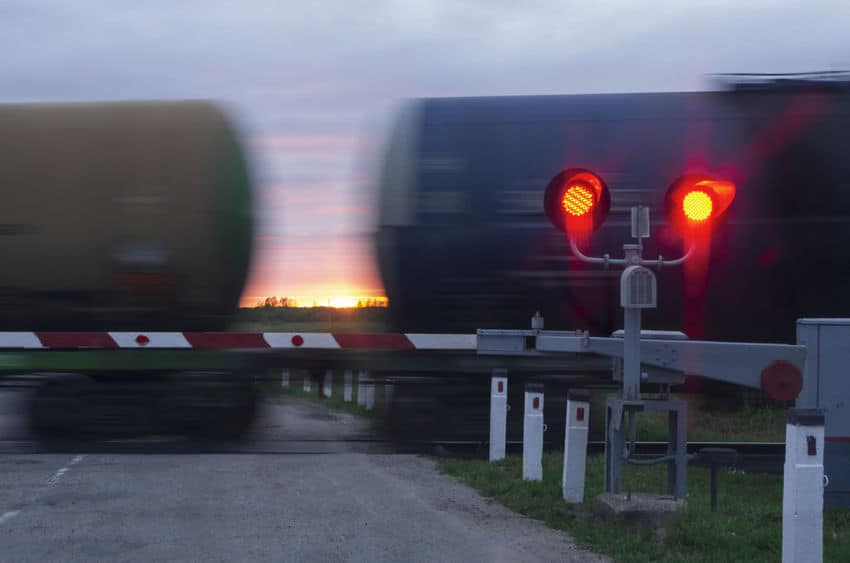 railroad lights lit up with a barrier down and a train behind it moving quickly on the tracks, a sunset is in the background