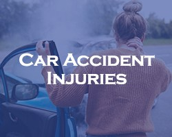 Car Accident Injuries -- blue overlay on a woman holding her neck after being in a car accident and standing next to her damaged car