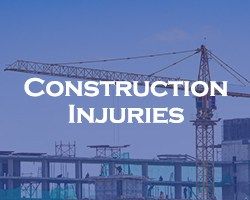Construction Injuries -- blue overlay on a view of a construction site and crane