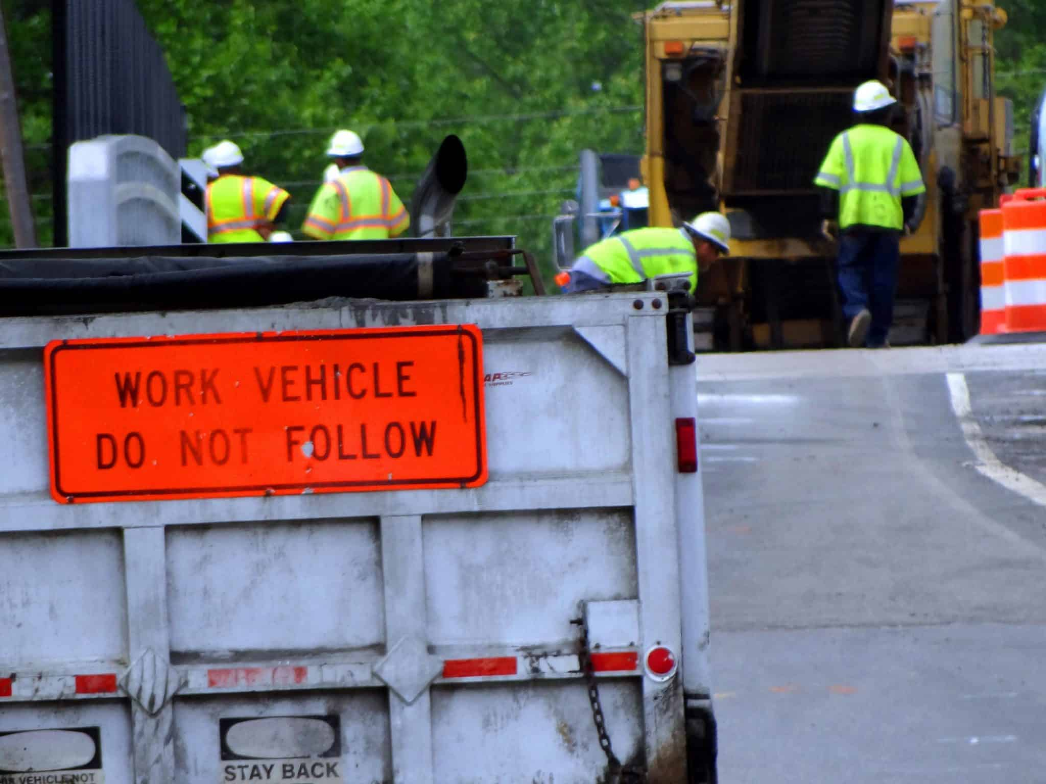 close up on a sign saying work vehicle do not follow with construction workers and equipment in the background