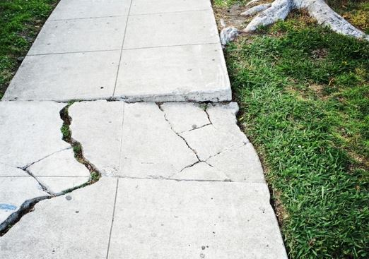 large crack in an uneven sidewalk