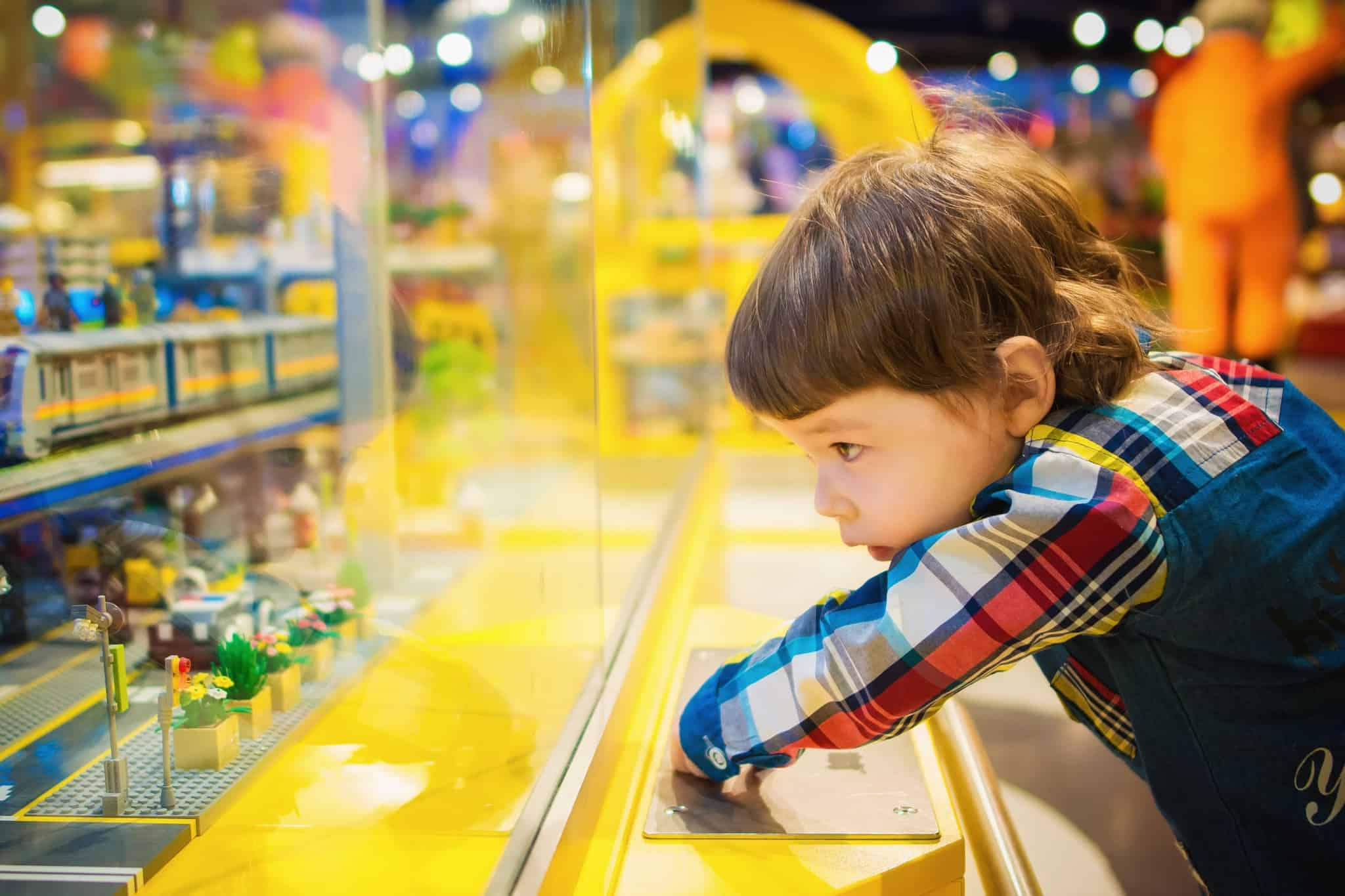 child looking at small toys through a glass wall