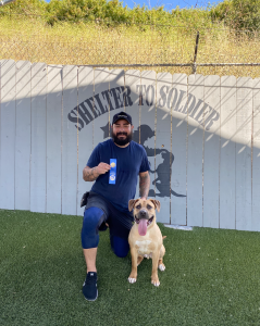 man with dog standing in front of a fence with the shelter to soldier logo on it
