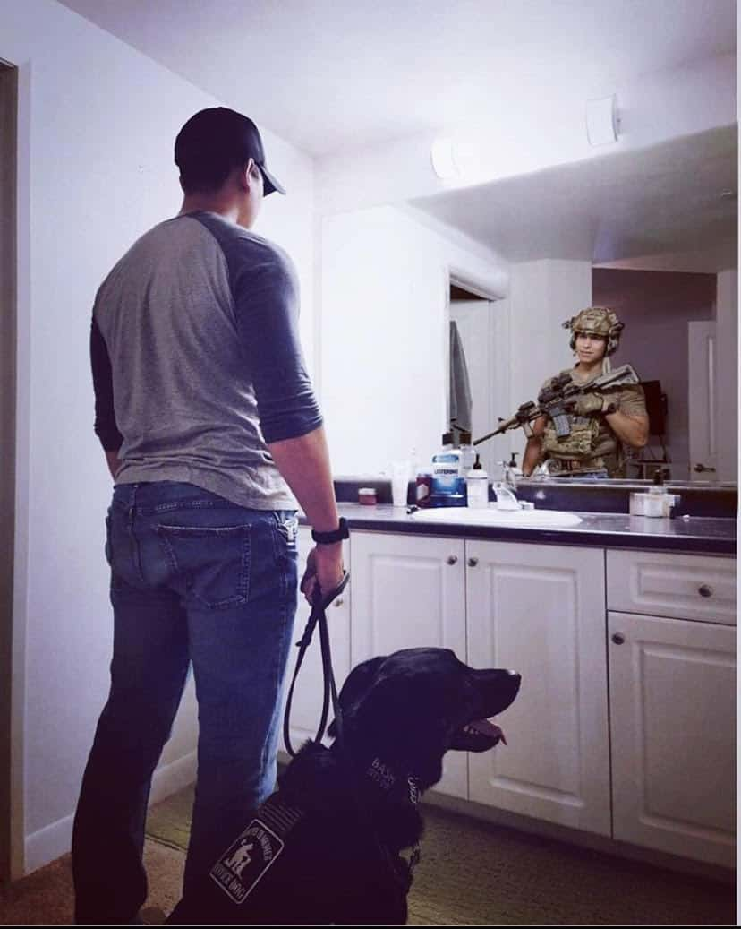 man looking in the mirror with his dog and the reflection shows the man in uniform