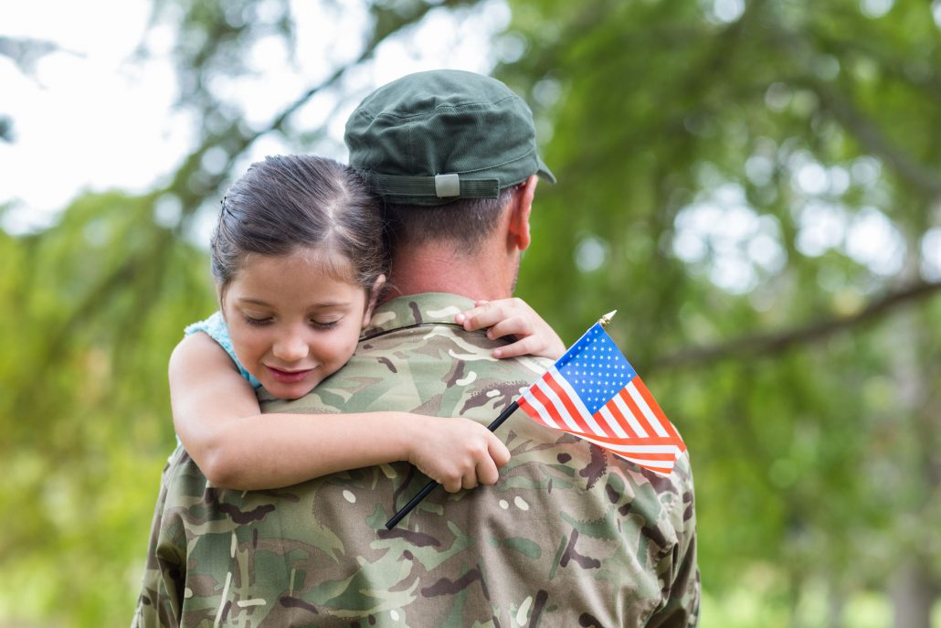 Soldier reunited and hugging his daughter on a sunny day