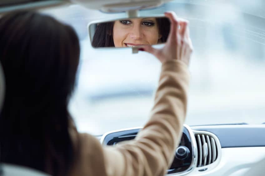 person fixing rear view mirror of the car while driving