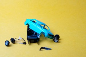 toy car broken into pieces after , wheels and glass fell off, yellow background