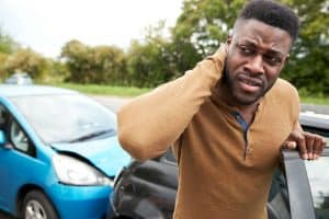 Male Motorist With A Whiplash Injury after a Car Crash Getting Out Of the Vehicle before calling The Barnes Firm Injury Attorneys